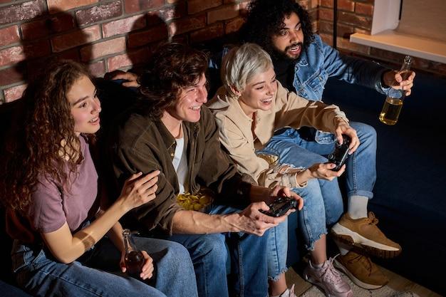 コンソールでビデオ ゲームをプレイするジョイスティックを持ったカップルの友人は、リラックスして座って楽しみます。カジュアルウェアを着た幸せな男性と女性が一緒に時間を過ごす