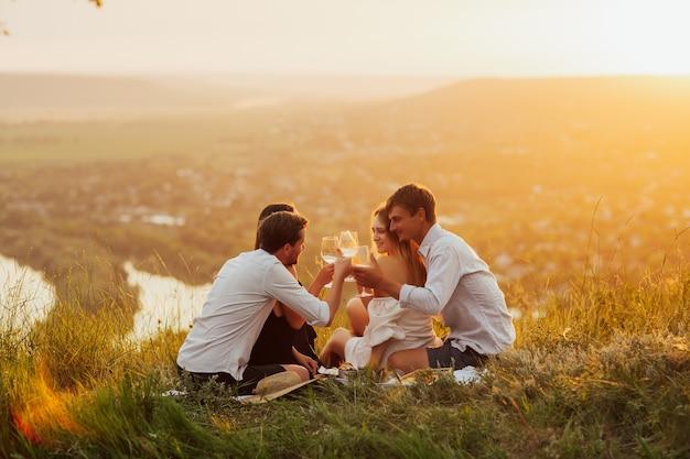 田舎でピクニックをしているカップル。ピクニックで川の水面に白ワインのグラスを持っている人。