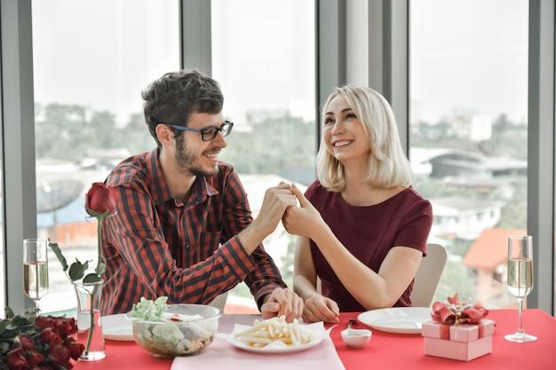 カップルが手をつないで、テーブルで結婚を提案する