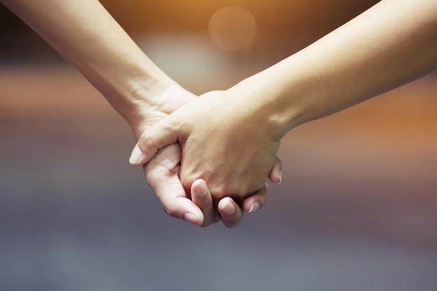 カップルは夜、ロマンチックな雰囲気で手をつないでいます。
