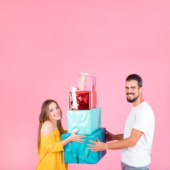 Couples holding colorful gift boxes stacked against pink background
