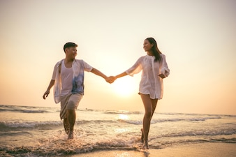 Couples holding hands Beach romp happily