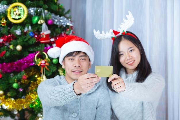 一緒にクレジットカードを保持しているクリスマス帽子のカップル
