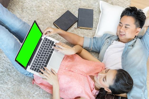 ラップトップを使って横たわっているカップル