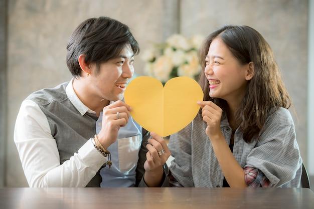 アジアの男性と女性のハートの形の紙を保持しているカップルの幸福の感情でカット、人々は概念的な愛