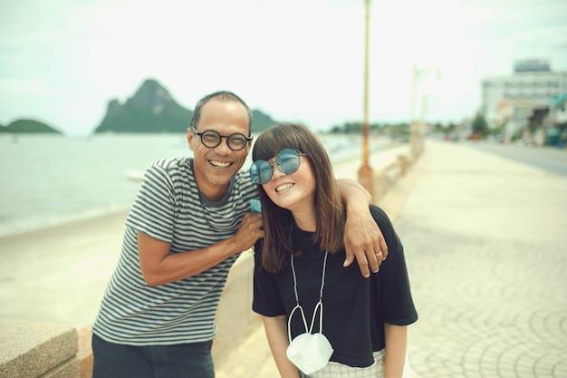 해변 옆에 서서 행복으로 웃고 있는 중년 아시아인 커플