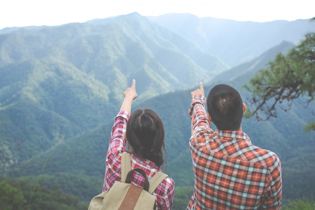 Пары, указывающие на вершину холма в тропическом лесу, походы, путешествия, восхождение.