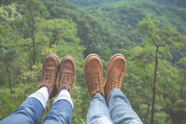 Couples raise their feet pointing to the hillside in tropical forests, hiking, traveling, climbing.