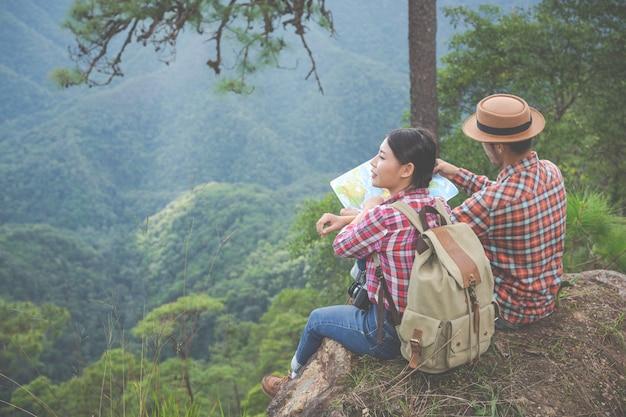 Пары видят карту в тропическом лесу с рюкзаками в лесу. приключения, походы, скалолазание.