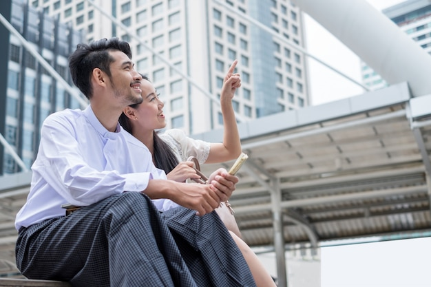 Couples sit holding dollars with point and looking at condominium