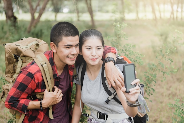 Couples using smartphones to take selfies