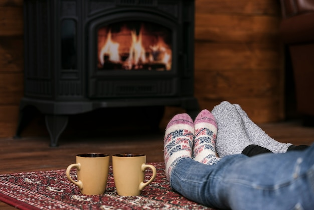 Couples warming feet next to fireplace
