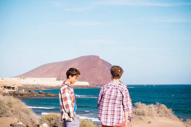 Couplpe of teenagers at the beach talking and looking at the sea to go surfing - caucasian 20s have fun and enjoy - beautiful background with small mountain and sky