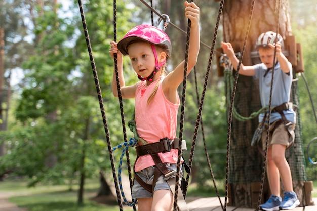 Bambini coraggiosi che si divertono in un parco avventura