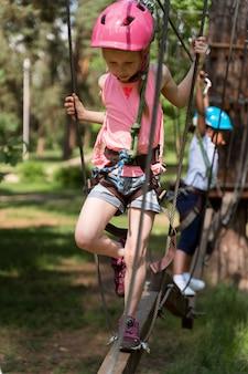 Bambini coraggiosi che giocano in un parco avventura