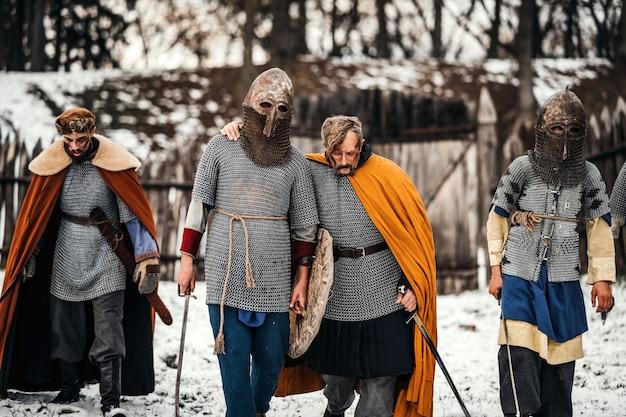 武器を手にしたヘルメットとローブを身に着けた勇敢な騎士が戦いの後に戻ってきます。戦争と歴史の概念