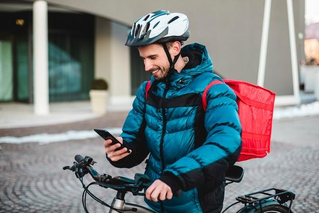 Курьерская доставка велосипедов, служба питания на дом. человек-курьер с помощью приложения карты на мобильном телефоне, чтобы найти адрес доставки в городе. еда, доставка, курьер, велосипед, 4g.