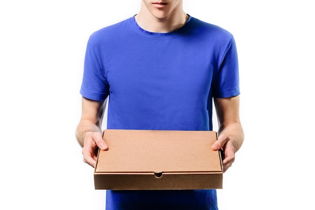 Courier in a blue t-shirt holds a box of pizza while standing isolated on a white