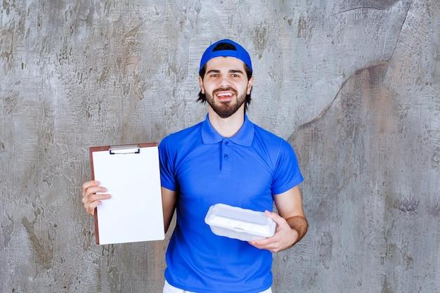 Corriere in uniforme blu che tiene una scatola di plastica da asporto e chiede una firma.