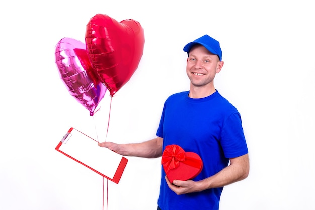 Courier in blue uniform holds red heart-shaped gift box and balloon for valentine's day