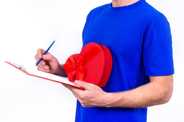 Courier in blue uniform holds red heart-shaped gift box for valentine's day and checks order on