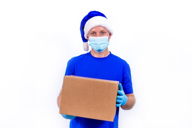 Courier in blue uniform, protective medical mask, gloves and santa claus hat holds gift box