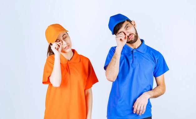 파란색과 노란색 유니폼을 입은 택배 소년과 소녀는 피곤하고 졸리다.
