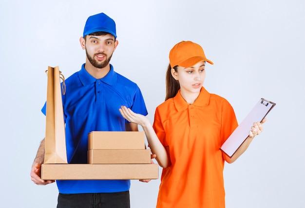 Курьерские мальчик и девочка в синей и желтой униформе держат картонные коробки для еды на вынос и пакеты для покупок и представляют список клиентов.