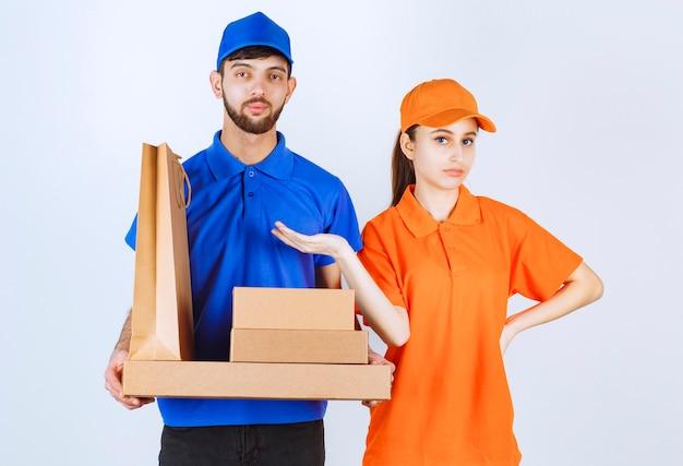 段ボールのテイクアウトボックスとショッピングパッケージを保持している青と黄色の制服を着た宅配便の男の子と女の子。