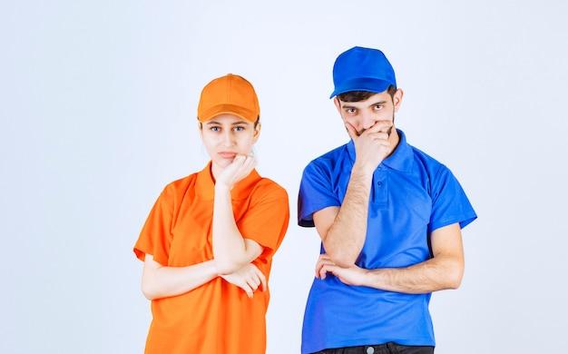 青と黄色の制服を着た宅配便の男の子と女の子は、混乱して思慮深く見えます。