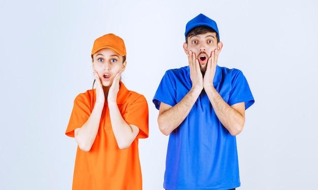 파란색과 노란색 유니폼을 입은 택배 소년과 소녀는 무섭고 겁에 질려 보입니다.