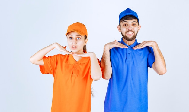 Courier boy and girl in blue and yellow uniforms giving lovely and cheerful poses.