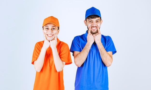 Corriere ragazzo e ragazza in divise blu e gialle che danno pose adorabili e allegre.
