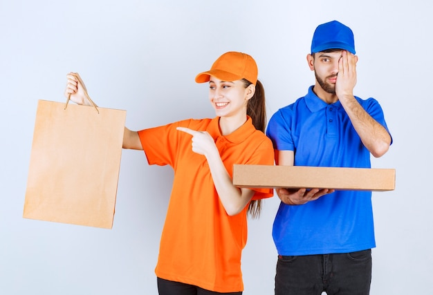 Courier boy and girl in blue and yellow uniforms holding cardboard takeaway boxes and shopping packages looks confused and terrified.