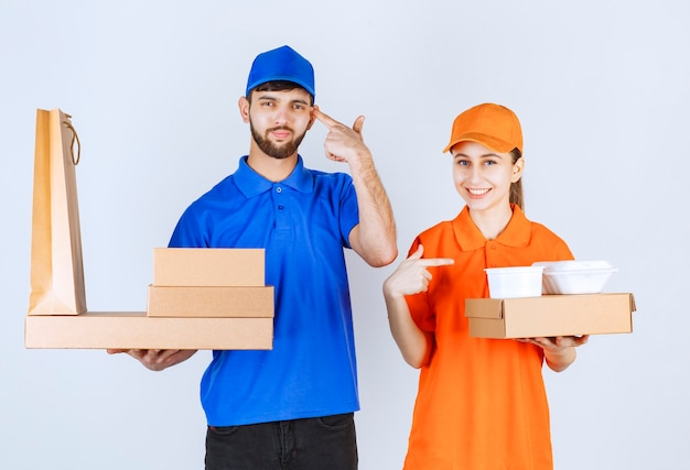 Courier boy and girl in blue and yellow uniforms holding cardboard takeaway boxes and shopping packages looks confused and thinking about new ideas.