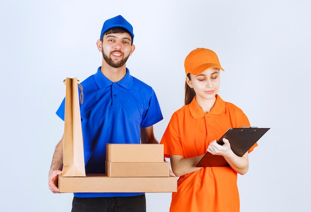 Courier boy and girl in blue and yellow uniforms holding cardboard takeaway boxes and shopping packages and presenting the customer list.