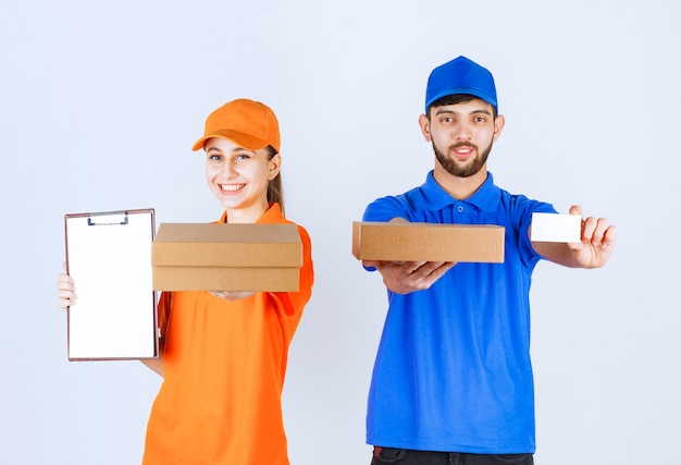 Courier boy and girl in blue and yellow uniforms holding cardboard takeaway boxes and shopping packages and presenting their business card.