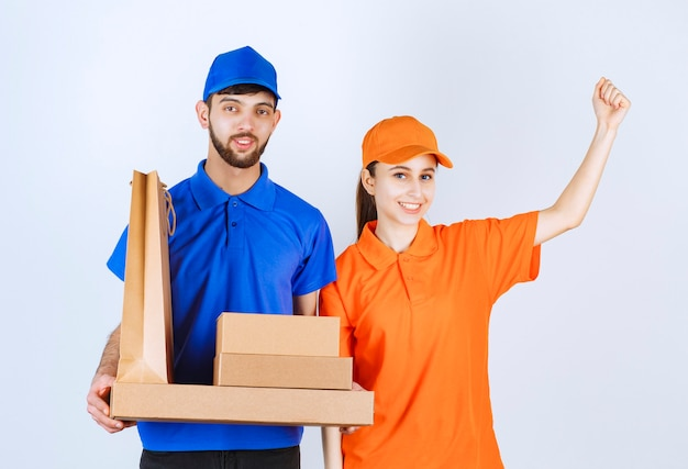 Courier boy and girl in blue and yellow uniforms holding cardboard takeaway boxes and shopping packages and showing their fists.