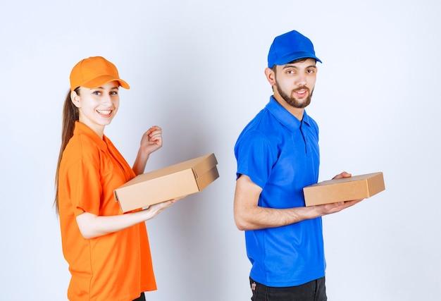 Corriere ragazzo e ragazza in divise blu e gialle che tengono scatole di cartone da asporto e pacchetti della spesa.
