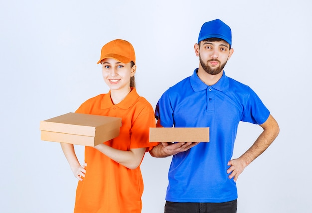 Courier boy and girl in blue and yellow uniforms holding cardboard takeaway boxes and shopping packages.