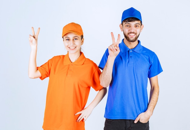 Courier boy and girl in blue and yellow uniforms showing enjoyment and happiness sign.