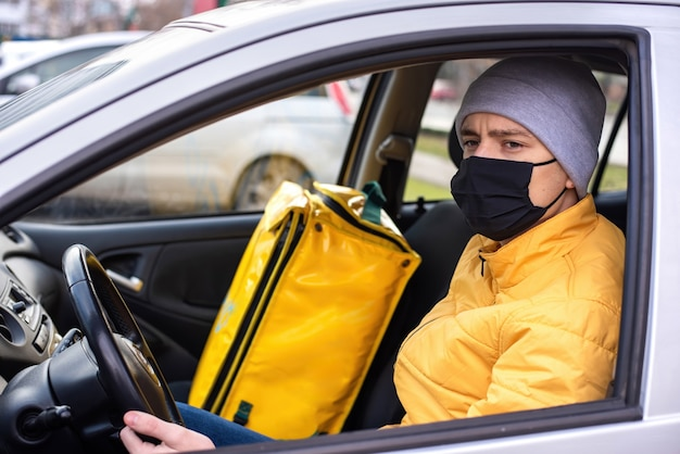 Courier in the car with black medical mask, delivery backpack on the seat. food delivery service