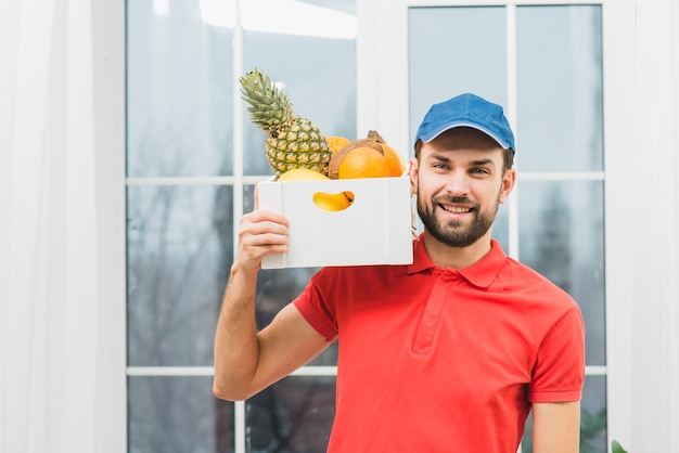Courier carrying fruits on shoulder