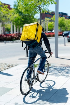 Курьер доставляет еду с желтым тепловым рюкзаком, едет на велосипеде по городу. концепция службы доставки еды