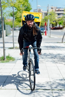Courier delivering food with a yellow thermal backpack, riding a bicycle in the city. food delivery service concept