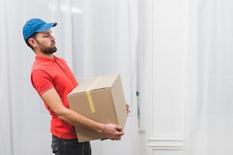 Courier delivering heavy parcel
