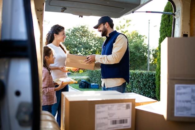 Курьер доставляет пакеты с игрушками женщине и маленькой девочке.