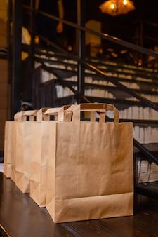 自宅での宅配便のフードサービス。女性の宅配便業者は、食べ物が入った名前のないバッグを注文しました。