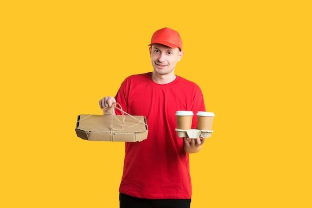 赤い帽子とtシャツの宅配便配達人は黄色の箱とコーヒーを保持します