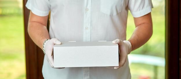 Курьер-доставщик в медицинских латексных перчатках и маске безопасно доставляет онлайн-покупки в белом ящике до двери во время эпидемии коронавируса covid-19. оставайся дома, безопасная концепция.